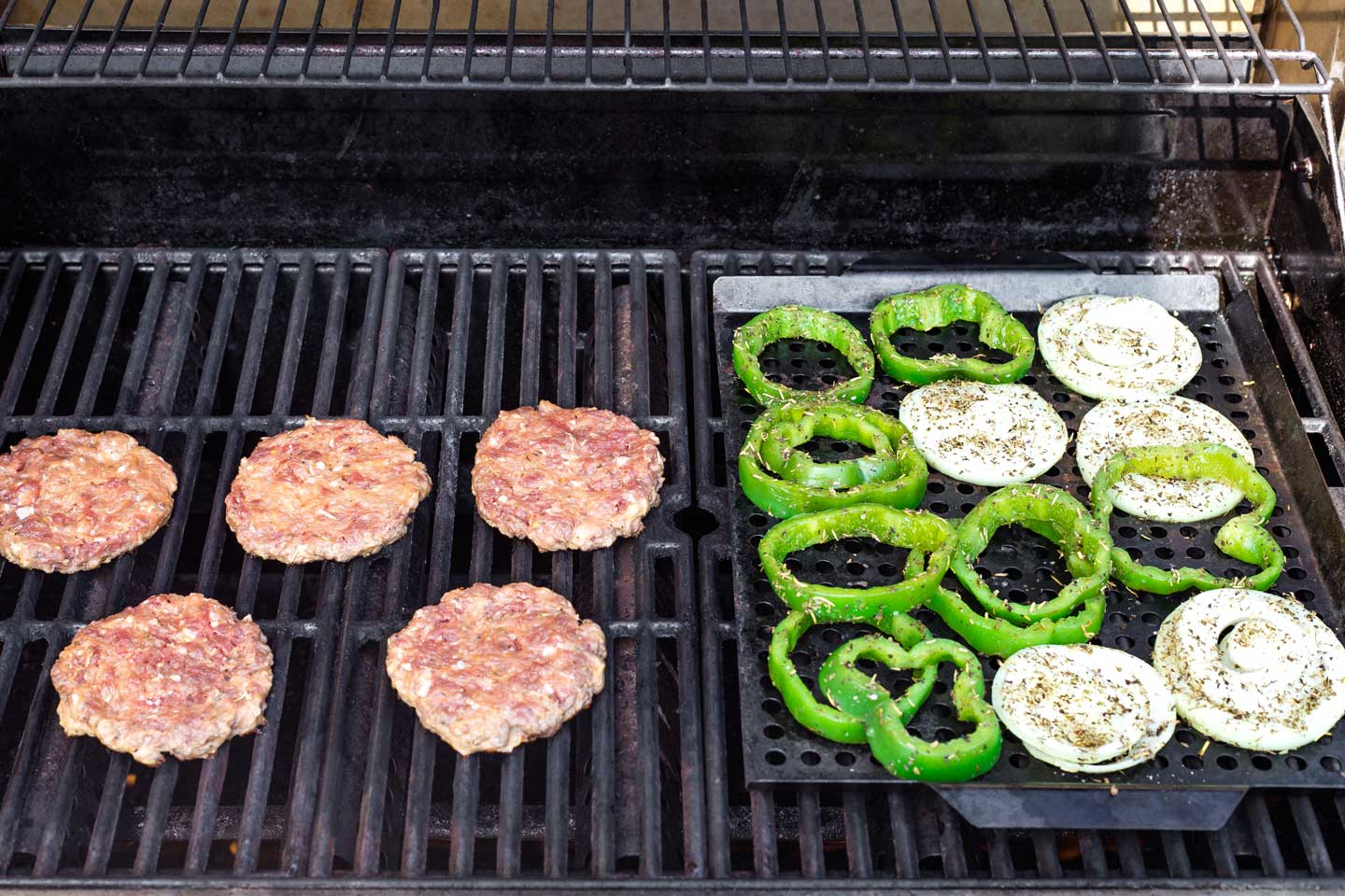 Hamburgers and veggies cooking on grill.