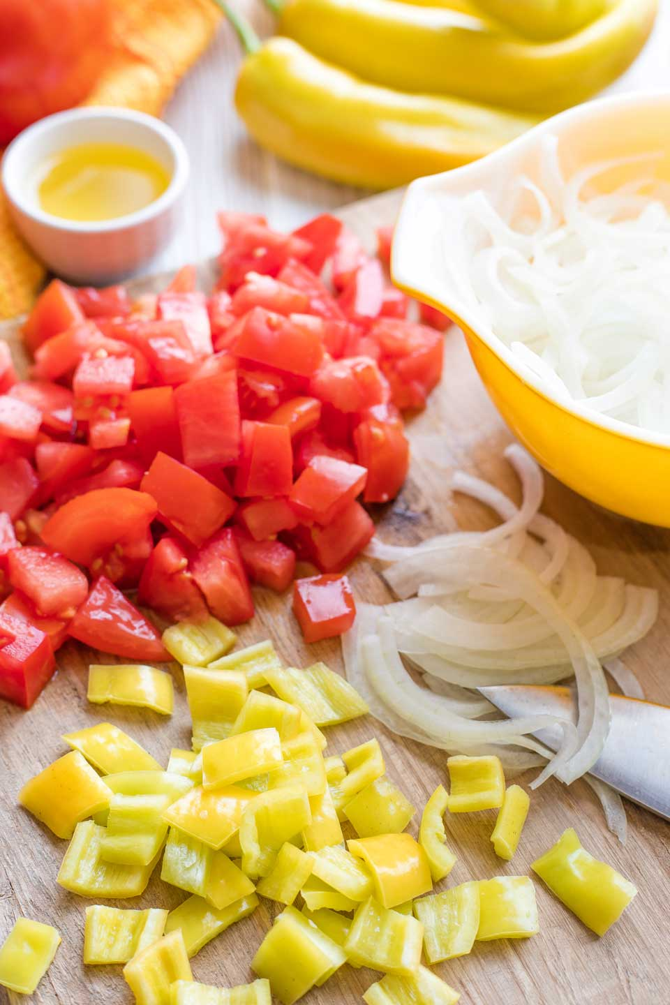 Cutting board with piles of cut tomato, onion and pepper, with salad bowl and other ingredients nearby.