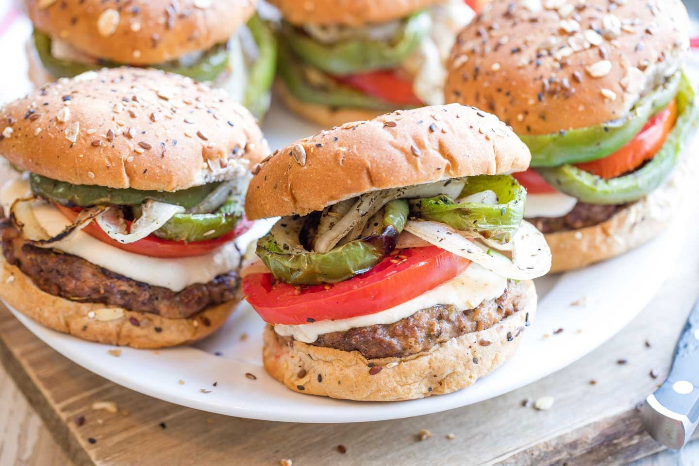 Five finished, grilled hamburgers piled with toppings on a large white serving plate.