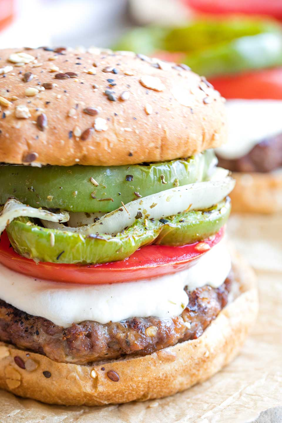Closeup of the right side of a completed hamburger topped with Italian vegetables, cheese and bun.