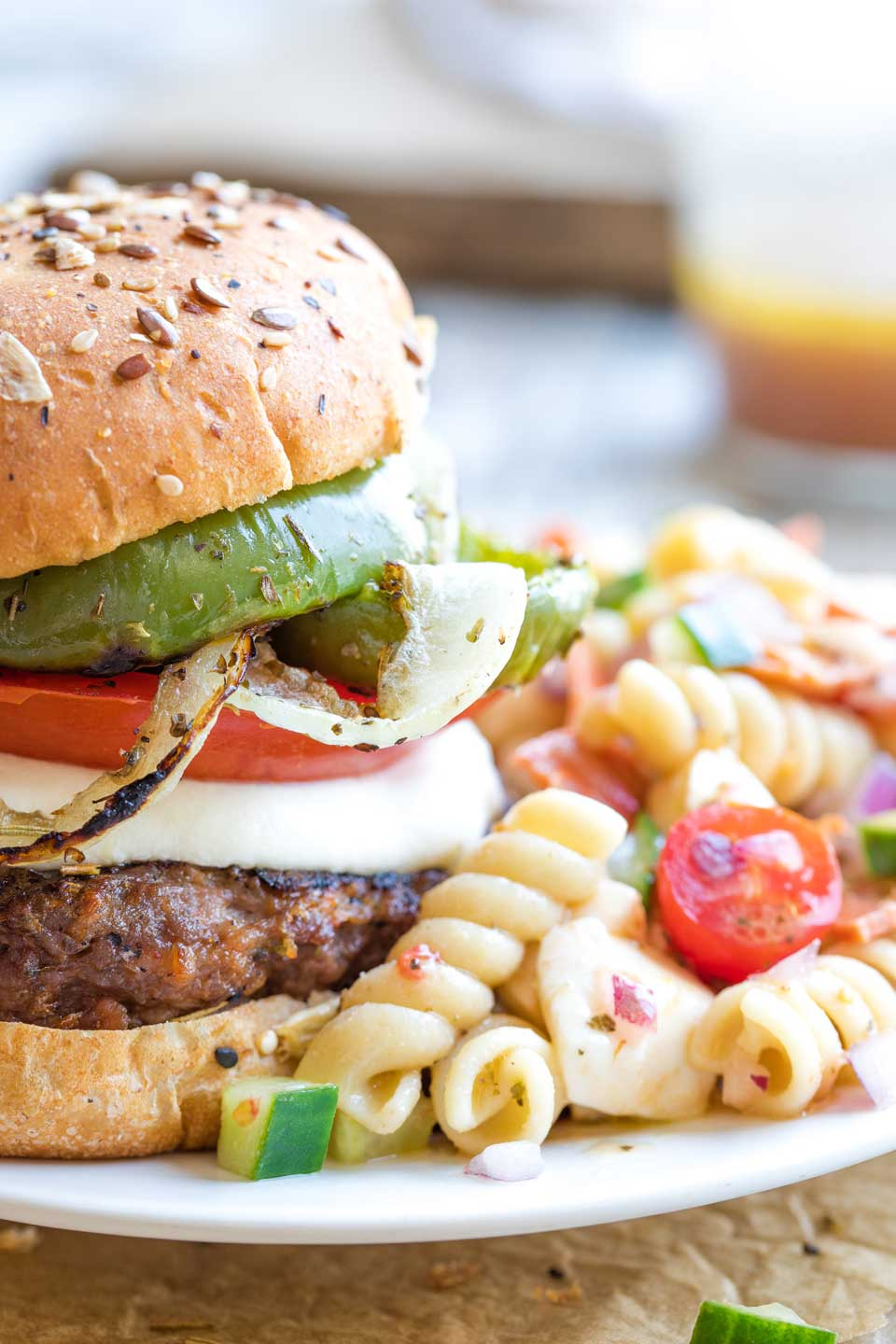 Closeup showing half of a grilled burger plated next to a mound of Italian pasta salad.