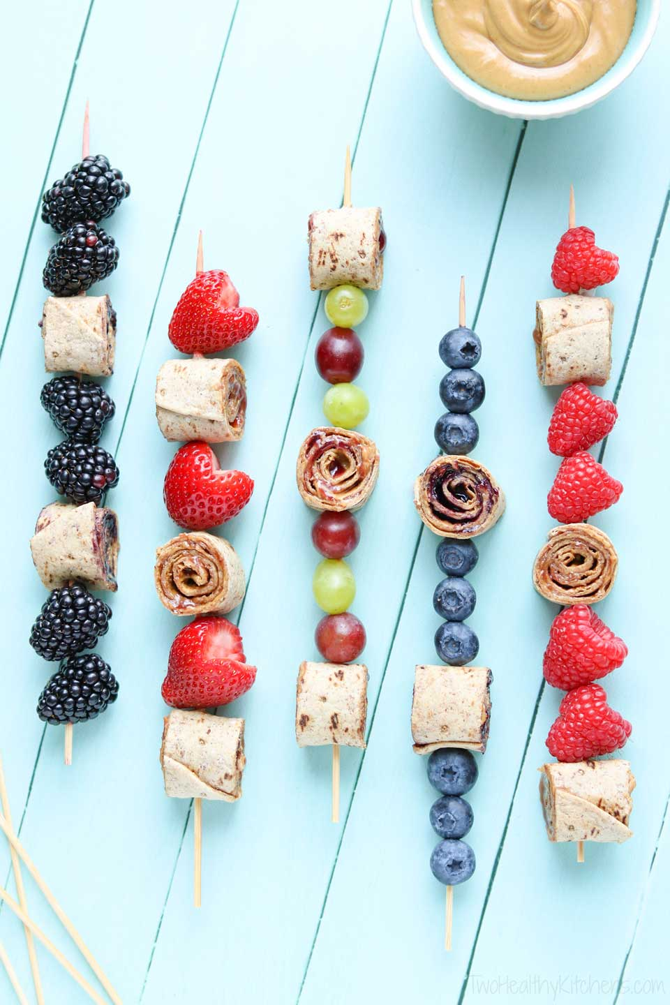 Overhead of pinwheels and fruit skewered on 5 sticks with a bowl of extra peanut butter nearby.