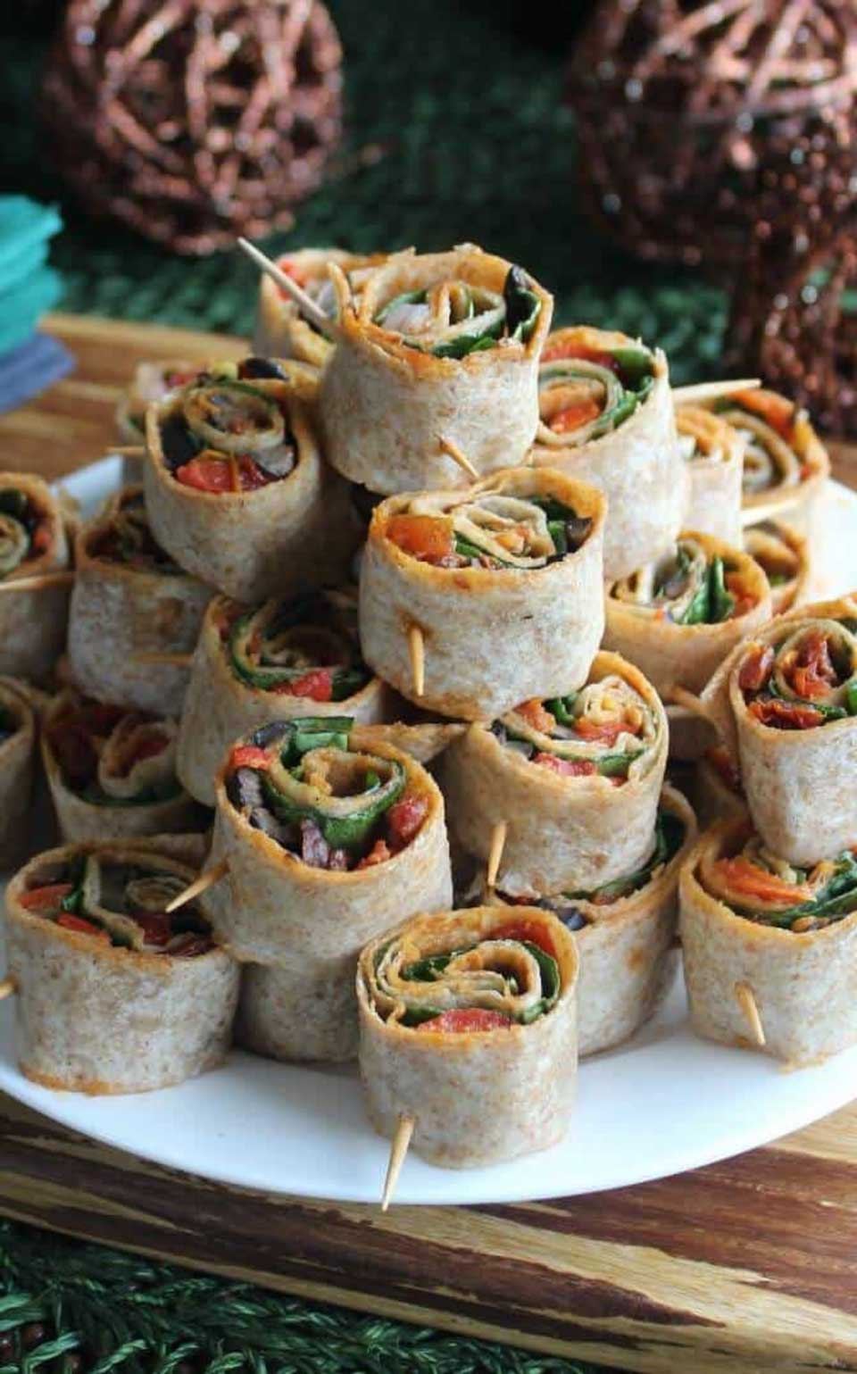 A big stack of Spicy Tortilla Roll Ups on a white plate with party decorations in the background.