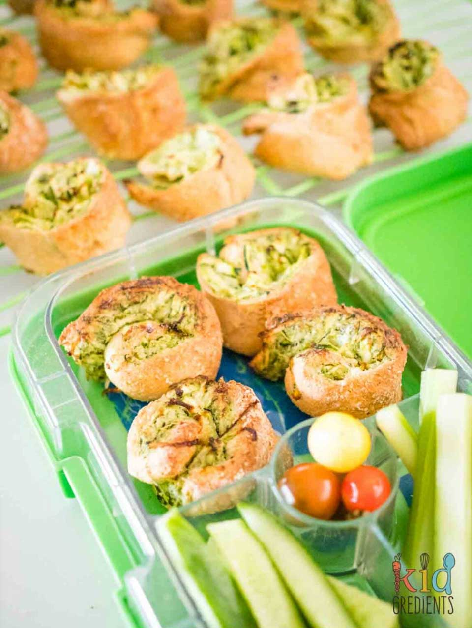 Four in a lunchbox, along with veggie sticks, with additional pinwheels on a cooling rack in background.
