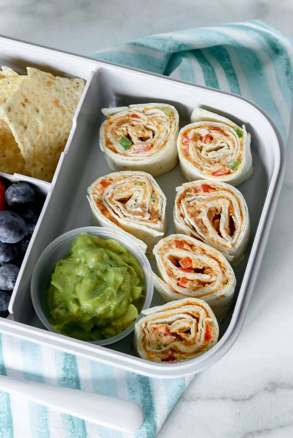 6 pinwheels in open lunchbox with bowl of guacamole on a teal striped napkin.