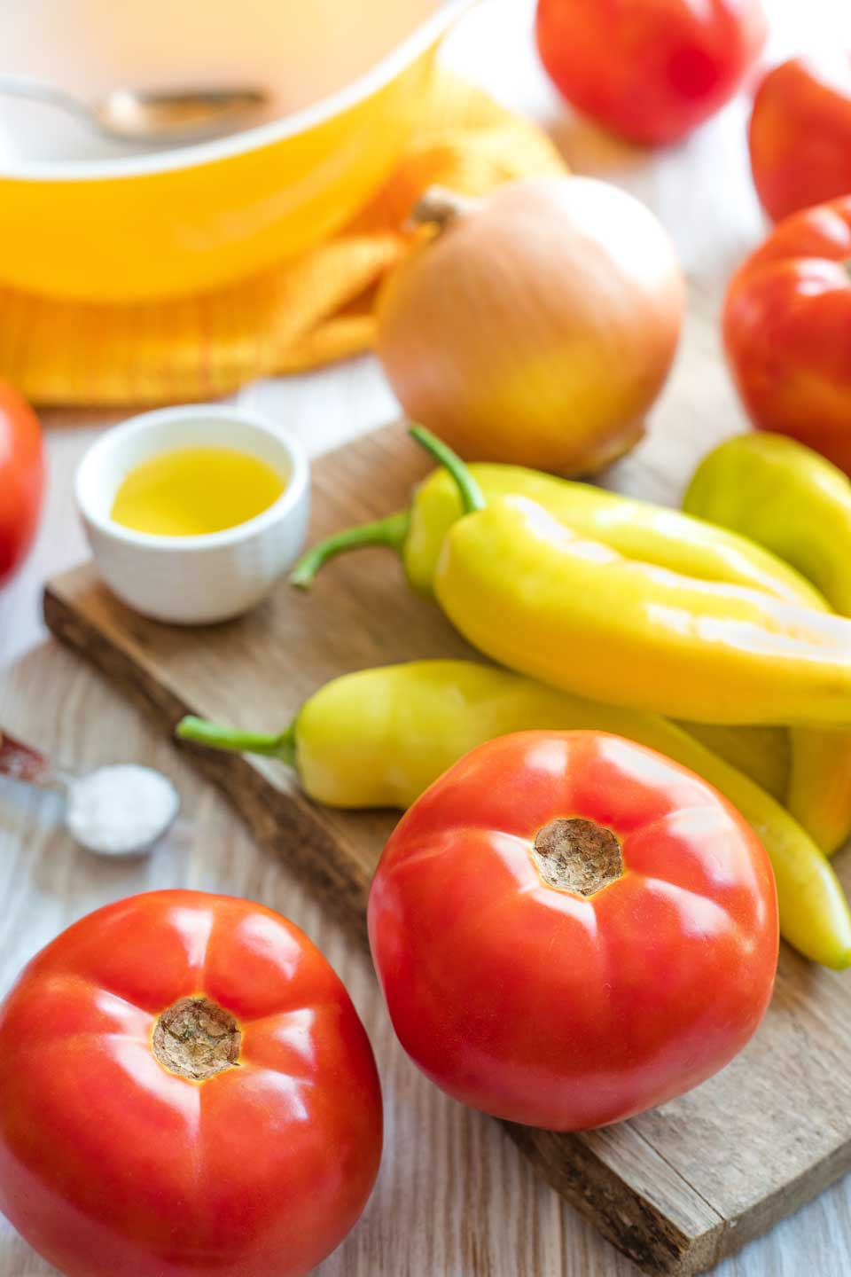 Two tomatoes, four yellow peppers and onion on cutting board, with extra ingredients and tomatoes nearby.