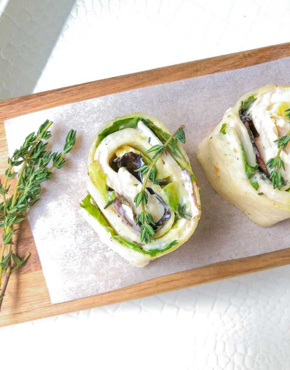Closeup of one of these tortilla roll ups on a paper-lined wooden serving tray, decorated with fresh thyme sprigs.