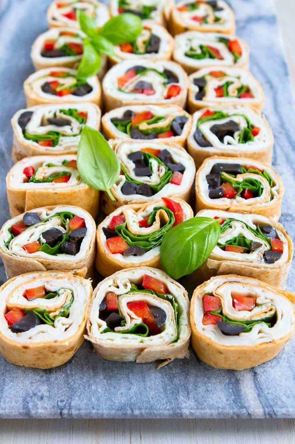 21 roll ups in 3 long rows on a marble serving tray, scattered with basil leaves for garnish.
