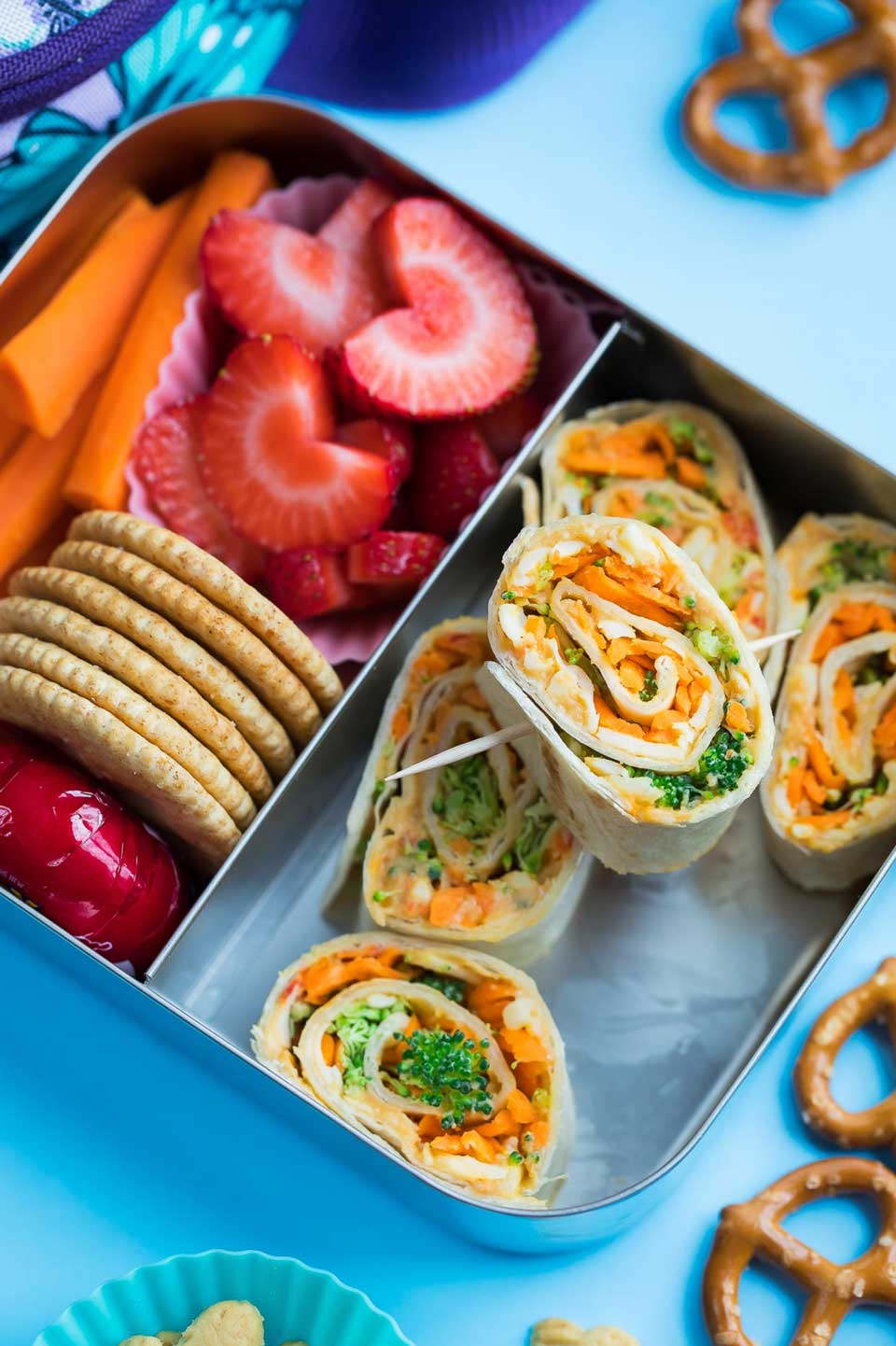 Open lunchbox with 5 of these roll ups in one compartment and carrot sticks, strawberries and crackers in a second area.