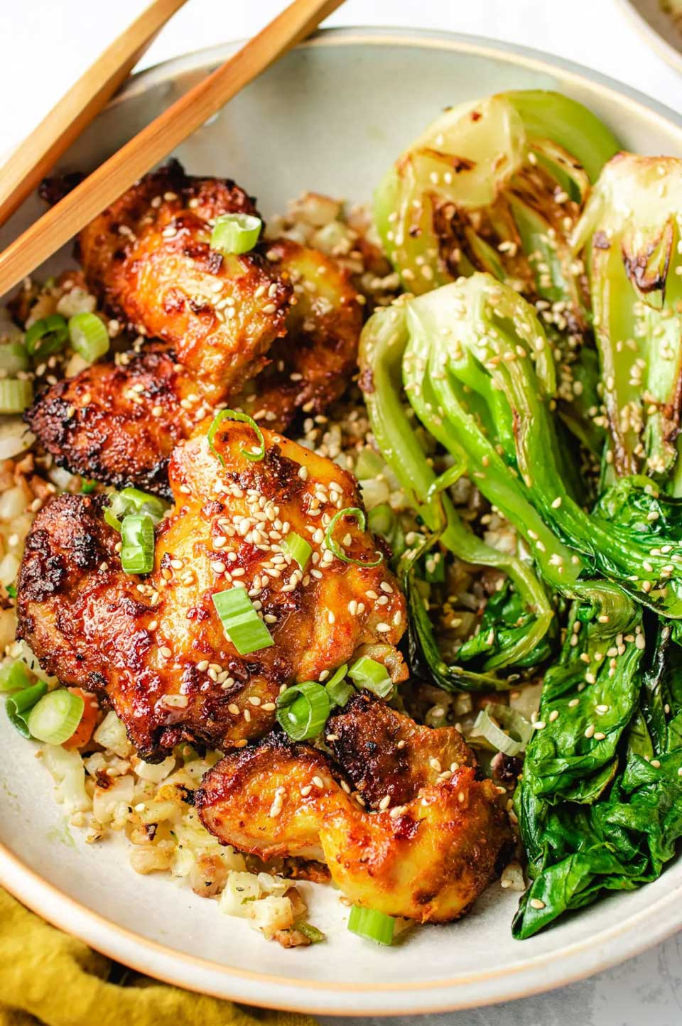 Air fried chicken nestled with rice and bok choy, with chopsticks across edge of plate.