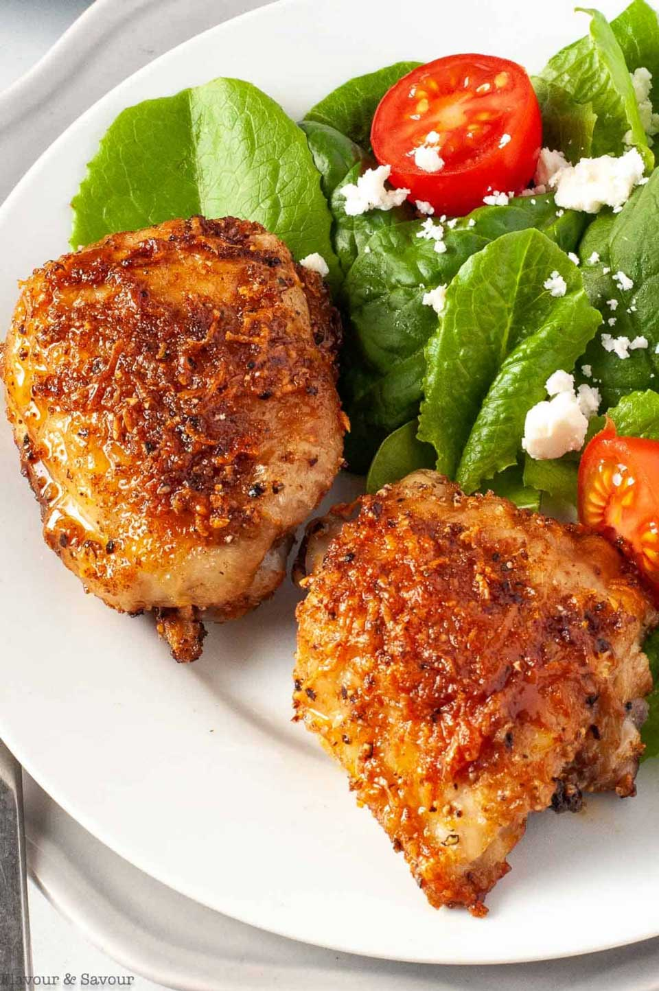 Two thighs on white dinner plate with tomato and feta salad along side.
