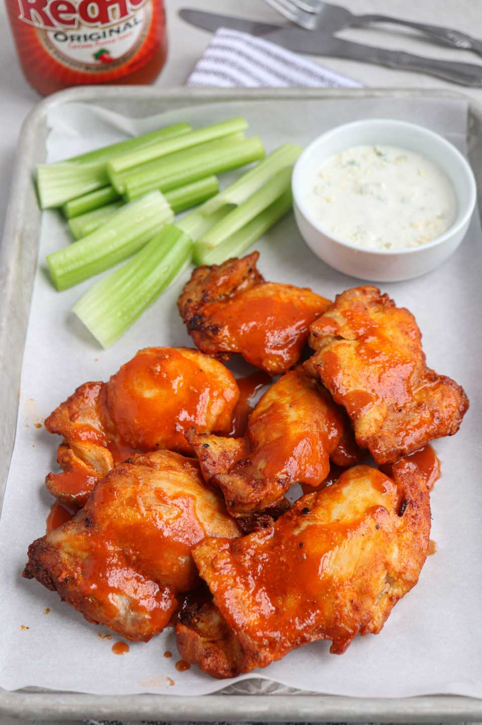 Several buffalo chicken pieces on paper-lined tray with ranch and celery sticks.