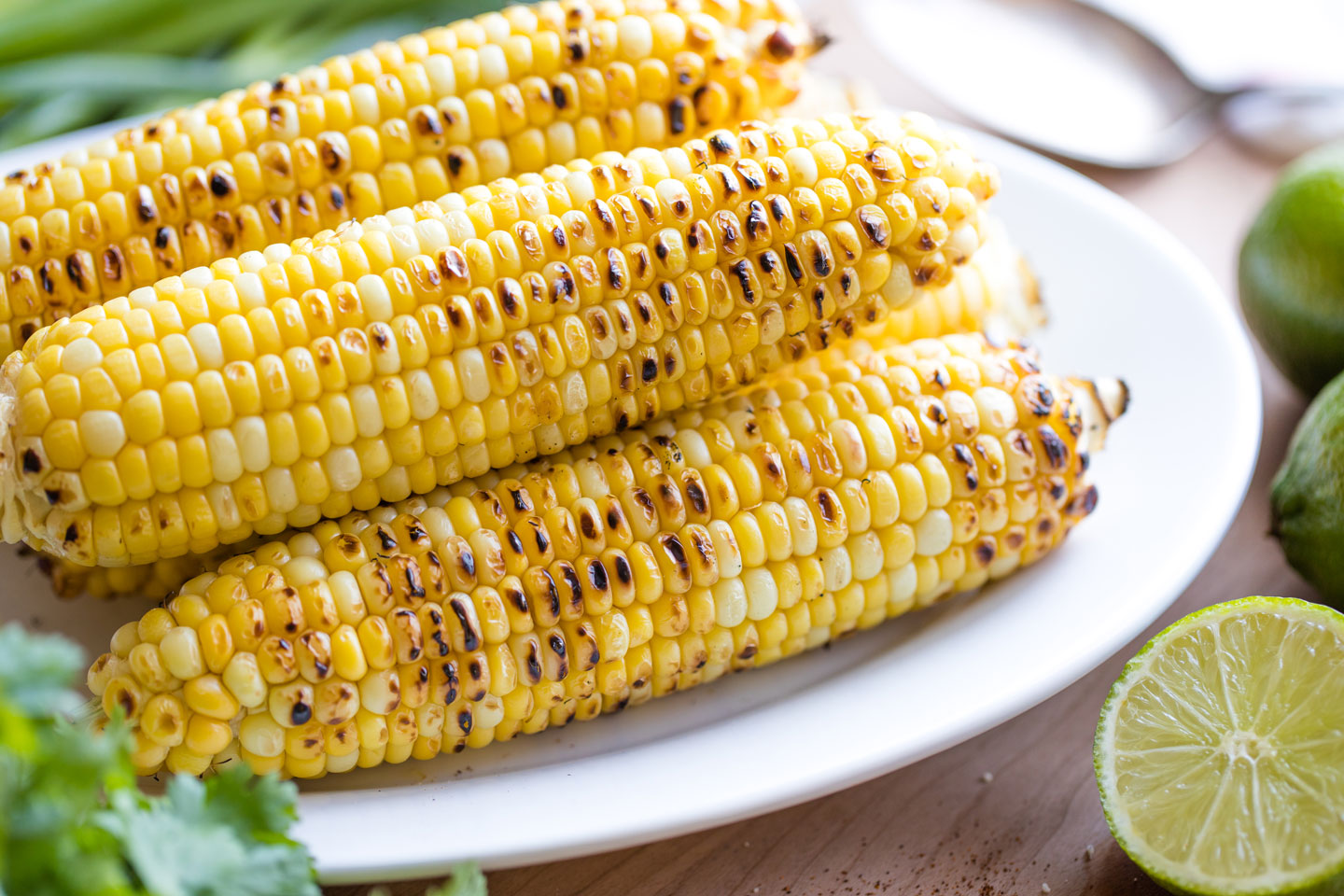 Closeup of several ears of grilled corn with sear marks, piled on a platter after cooking.