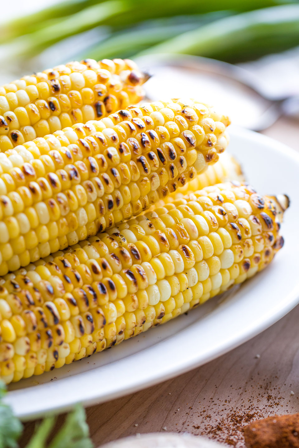 5 ears of grilled corn on the cob on a white platter, with pretty greens and spices nearby.