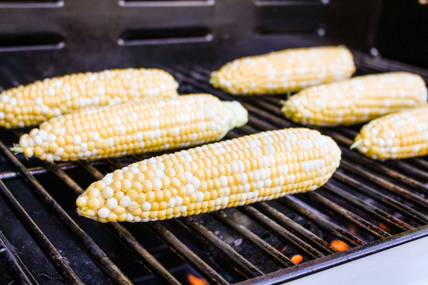 6 ears of husked corn on the cob, just laid on the grill to start cooking.