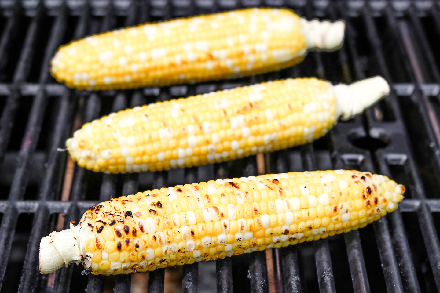 3 ears of corn on the cob on the grill that are almost done cooking, with brown spots visible.