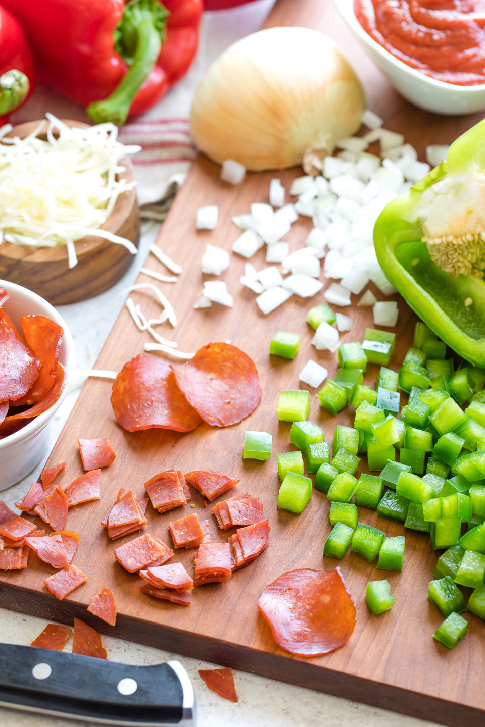 Cutting board surrounded by ingredients and covered in diced peppers, onions and pepperoni.