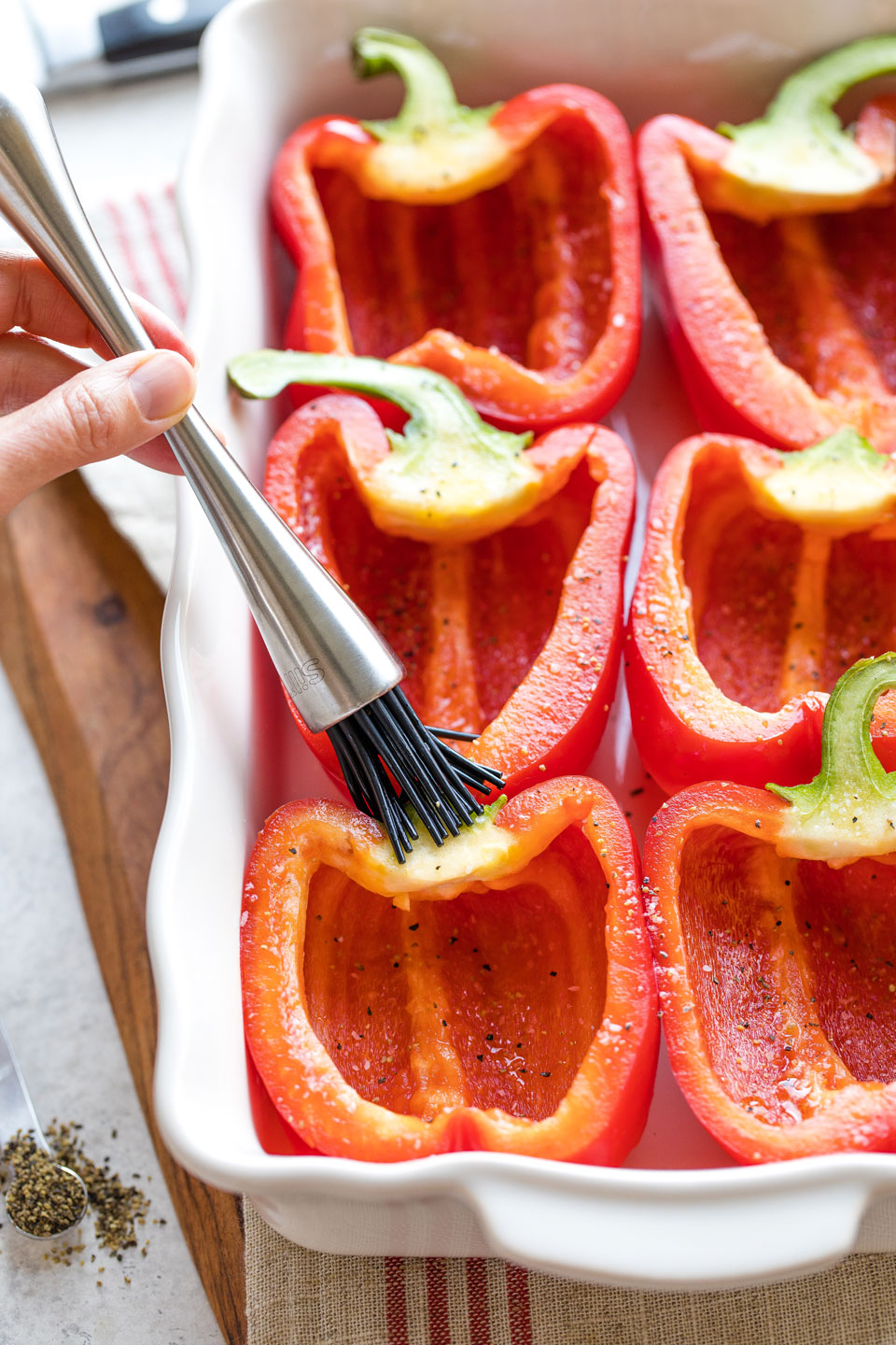 Hand brushing oil onto un-stuffed peppers in baking dish.