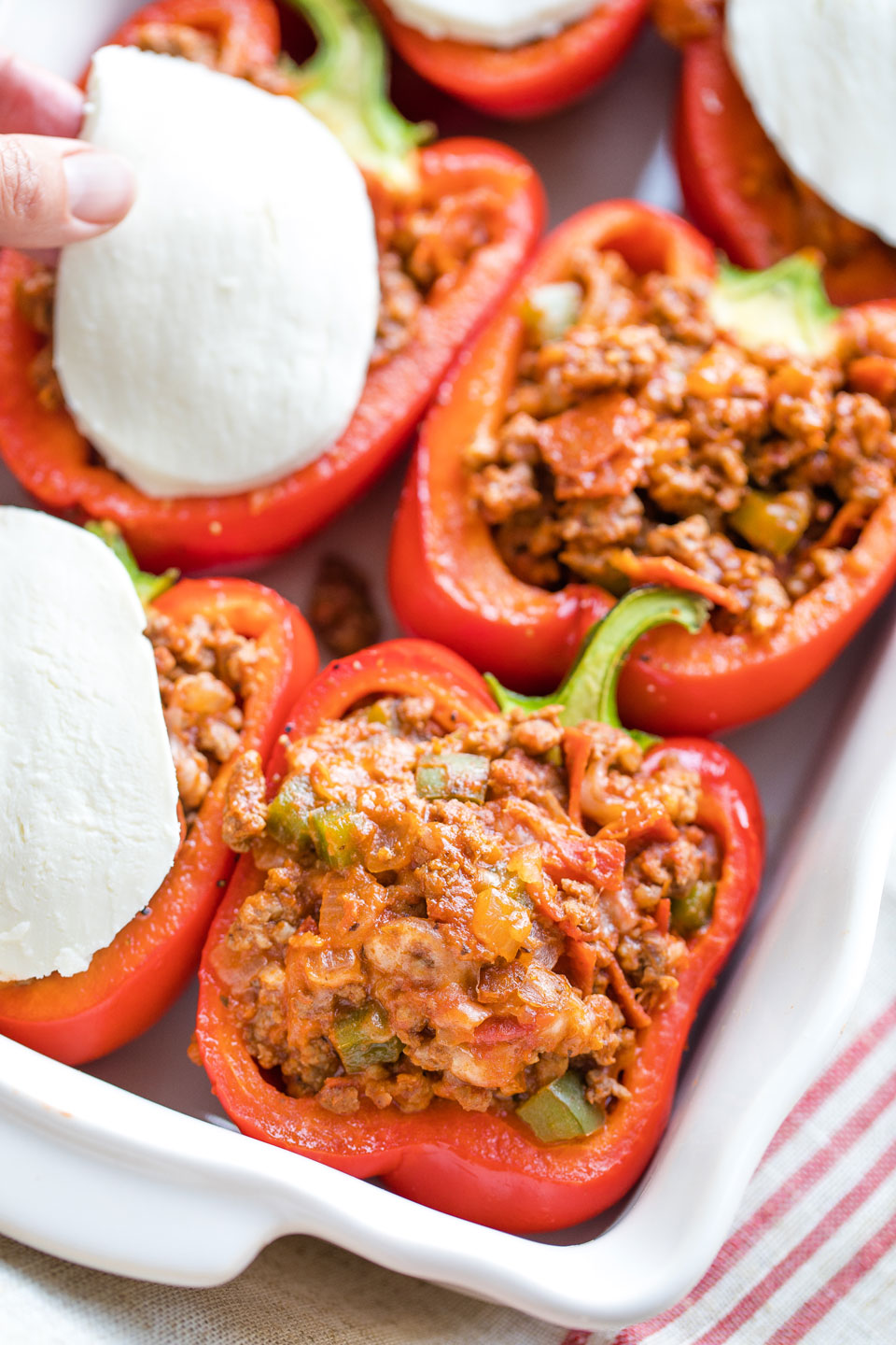 Peppers stuffed in baking dish with hand laying mozzarella on top.