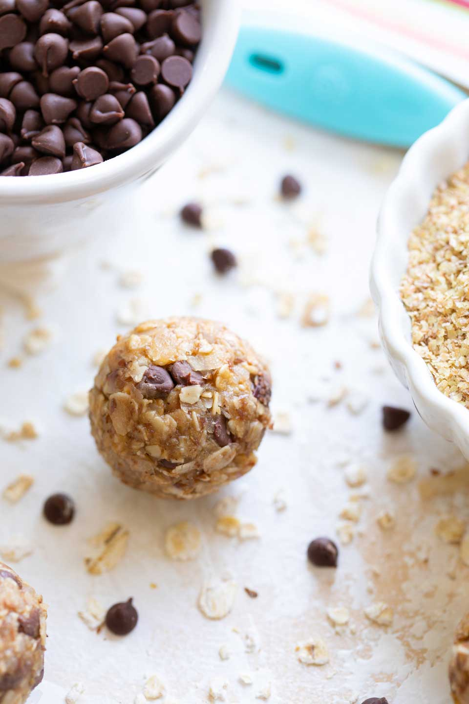 Closeup of one healthy Energy Ball laying between bowls of chocolate chips and wheat germ.