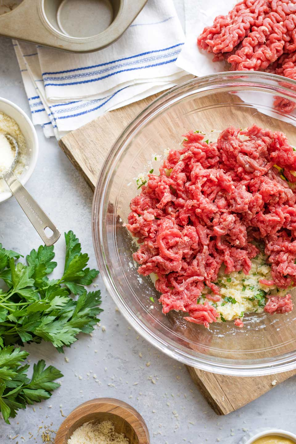 Ground beef crumbled into mixing bowl on top of other meatloaf ingredients.