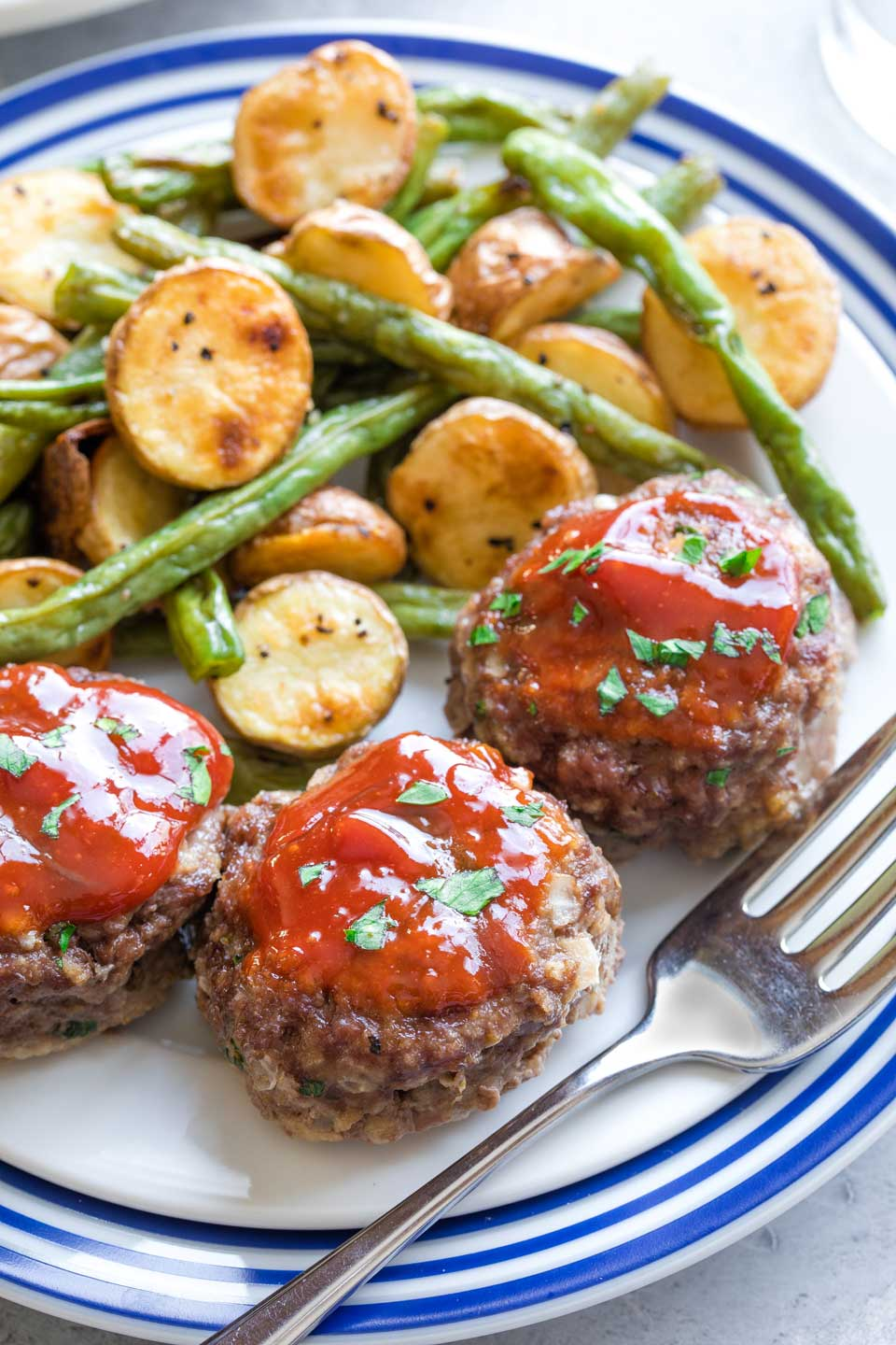 Serving suggestion of meatloaf muffins with roasted potatoes and beans.